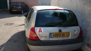 Back of a city car with a magnetic A-disk: red A in a white circle